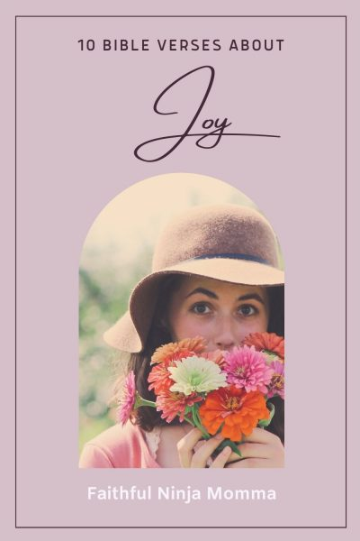 woman wearing hat holding flowers in front of her face